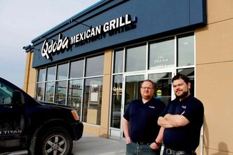 Business partners Curtis Palmer (left) and Ryan Morton stand outside Qdoba Mexican Grill, which opened its doors at 1-1340 Ellice Ave. on April 21.