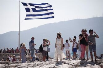 Tourists walk on the ancient Acropolis Hill beneath a Greek flag, in Athens, on July 3, 2013. THE CANADIAN PRESS/AP, Petros Giannakouris