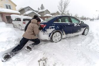 Residents of St. Thomas, Ontario push a snow bound car Sunday, November 24, 2013. THE CANADIAN PRESS/ Geoff Robins