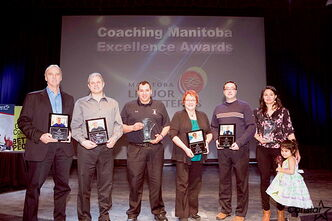The Coaching Excellence Award winners pose with their plaques.