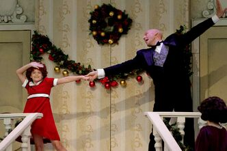 Annie, played by Zoë Adam, with Daddy Warbucks, played by Kevin Aichele, perform during a past production of Annie at Rainbow Stage. Many residents of River East work to help make Rainbow Stage a success.