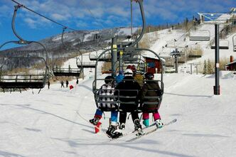 A group of brave skiers board the chairlift on their way to ski down the slopes of Colorado.