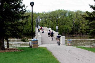 Cyclists cross the Assiniboine River in Assiniboine Park.