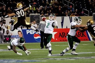 The Bisons' Mitchell Harrison makes a wild leap to get in the path of Huskies quarterback Drew Burko.