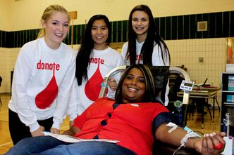 Melanie Paragg (front) is comforted and encouraged by her Grade 10 students Shaye Kemball (left), Patricia Neameyer (centre) and Ayla Zimmerman (right) while donating blood.