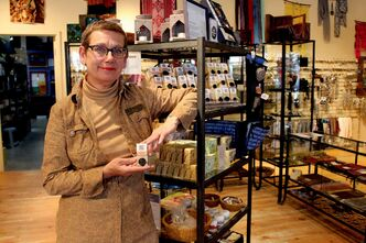 Gwen Repeta with some hand-made soaps offered at Ten Thousand Villages.