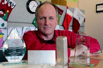 Michael Gupton of KMG Gold poses next to some silver and gold and the two Better Business Bureau awards the company was presented with in 2013.