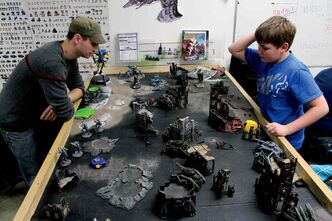 Jeff Fulham (right) and Sean Thiessen enjoy a game of Warhammer 40K at Maxx Collectibles.