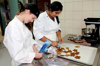 Shantel Laycock (left) and Sakshi Saul, Grade 8 students at General Byng School, put the finishing touches on some cookies in Winnipeg Technical College's culinary arts classroom during a day of hands-on experience for students in the Pembina Trails school division. (JORDAN THOMPSON)