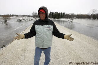 Rick Praznik hopes this raised gravel road separating the Red River, left, and homes, right, will help his neighbours down River Road avoid any more flooding. His house is far enough away and is raised, but two of his neighbours had their homes flooded by the ice jam last week.