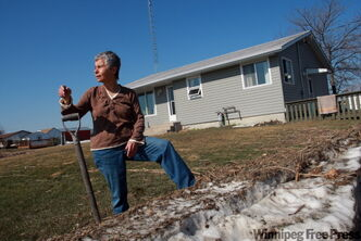 Joyce Ward cleans up after ice and water crossed Breezy Point, flooding her basement and causing major water damage.
