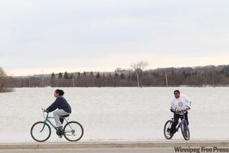 Flood watchers ride their bikes along 18th St. N just south of Grand Valley Rd. where fields are submerged by flood waters on Sunday evening.
