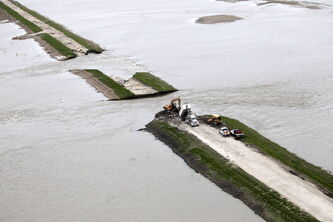 Water from the Portage Diversion spills over into neighbouring fields.