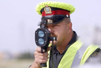 A Winnipeg Police Service officer uses a traditional laser speed-detection device on Bishop Grandin Boulevard in this file photo.