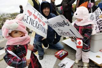 Twins Olivia, left, and Katelyn Stein, 2, with their uncle, Jeffrey Kohut, during the Occupy Winnipeg protest in front of the Manitoba Legislative Building.