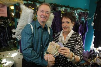 Peppertree Fashions owner Connie Hall hands thousands of dollars to Kevin Rollason.
