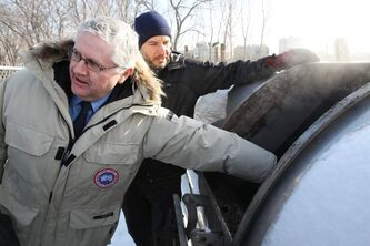 Conservation Minister Gord MacKintosh sticks his hand in the Biovator to feel the heat it generates. The Biovator is a composting unit that is converting all the food waste at The Forks and the University of Winnipeg into compost.