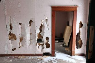 Smashed walls are visible in one of the homes at the Criddle-Vane Homestead after vandals caused damage to the provincial heritage park.