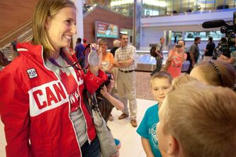 Olympic rowing silver medallist Janine Hanson shows off her medal to a gathering of fans that awaited her arrival by plane in Winnipeg Wednesday night.
