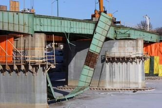 Two large cranes moving a massive piece of the old Disraeli Freeway had their load buckled and slid down towards the Red River on Tuesday.