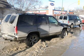 Vehicles go through water on Stafford Street near Corydon Avenue.