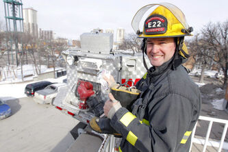 Firefighter Chad Swayze takes the first donation from the boot at the Osborne Street fire station.