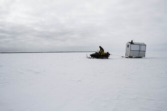 Kenyon pulls a wooden shack on skis behind his snow machine onto Lake Manitoba. The shack contains a stove so the fishermen can warm up on cold days.
