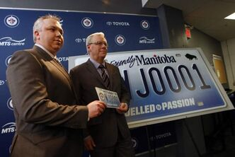Winnipeg Jets True North Foundation executive director Dwayne Green (left) and Premier Greg Selinger announce the raffle of the first printed  Jets specialty licence plate # WJ0001.