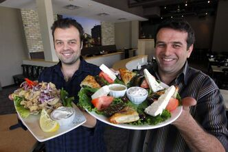 George Simeonidis and Stavros Chatjiathanasiadis, owners of  Santa Lucia Pizza on Corydon Avenue, with the restaurant's calamari and Greek Sampler plate.