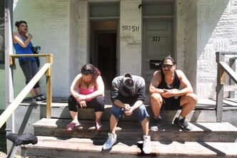 People gather on the front porch of a Spence Street rooming house.