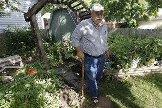 Marvin Gordon uses a cane to get around his garden. He still lives in pain seven years after contracting West Nile virus.