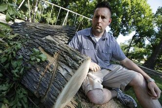 Jason Booth sits next to what remains of a tree in Fraser's Grove Park that he noticed had been cut in such a way that it might fall on a popular swing set.