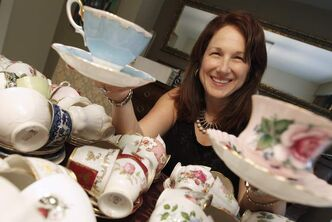 Sandra Lorange, a Guardian Angels committee member, shows off some of the donated teacups for an upcoming CancerCare fundraiser.