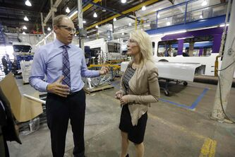 Cabinet minister and Manitoba MP Candice Bergen tours the New Flyer bus plant in Transcona with New Flyer's David White Wednesday.