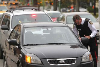 Police Insp. Jim Poole hands out cellphone tickets to drivers on Osborne Street Friday.