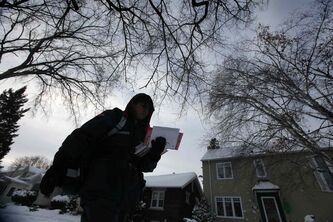 A letter carrier with Canada Post makes his way toward Grosvenor Avenue in River Heightsin on the mid-December day Canada Post announced the end of home delivery mail service.