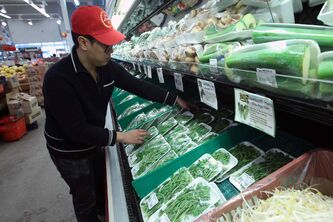 Kevin Trinh arranges packages of fresh herbs at Lucky Supermarket.