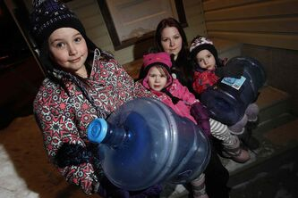 Kaylee Mack and her three young daughters (from left to right) Maykenzie, Gracelyn, and Keanna head out to get water at their grandparents' home Monday. They have been without water for 8 days.