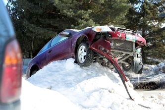 A car precariously rests high on a snowbank on St. Vital Road as police investigate the scene of a two-car collision Saturday.