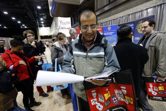 Ret Basnet, 47, peruses some documents he picked up at the job fair Wednesday.