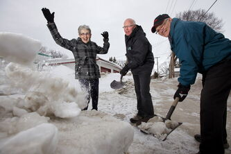 Susan McVarish cheers Monday as Good Samaritans Murray Greenley (centre) and Del Comerbach remove a windrow in front of her garage in the back lane of Helmsdale Avenue.