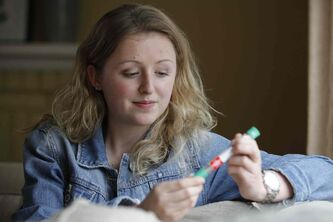 Hannah Lank, 16, who has life-threatening allergies to peanuts and tree nuts, holds an epinephrine autoinjector. She's dedicated to raising allergy awareness.