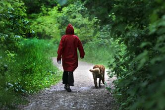 Brenlee Muska walks with her ten-year-old dog Adidas in Lagimodiere - Gaboury Historic Park in the rain Saturday.