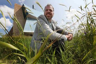Landscape expert Bob Somers crouches in tall grass around the human rights museum. The intent is to get 'as close to a tall grass prairie here as one can,' he says. s