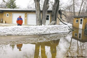 Don Kowalchuk surveys the swollen Souris River from his home on the banks of the river in Souris on Friday afternoon.