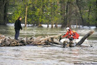 A man awaits rescue from driftwood at The Forks Saturday.