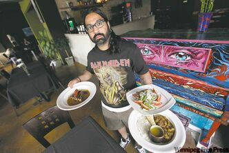 Robin Maharaj, chef and owner of Deadfish Cafe in Osborne Village, with bread pudding, arugula salad and curried goat.