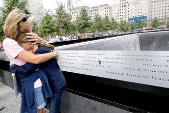 Celeste Pocher embraces her daughter after finding her brother-in-law's name, John Pocher, at the north pool at the National September 11 Memorial in New York City Sunday.