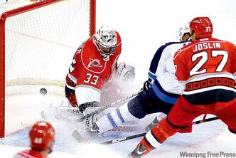Jets forward Evander Kane scores against Carolina's Brian Boucher in front of Derek Joslin (27).