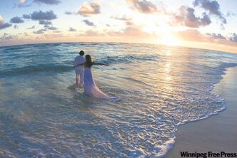 Bride and groom take the plunge after getting married on the beach in Punta Cana.